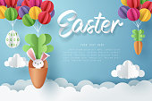 Paper art of Bunny in carrot and Easter eggs hang on colorful balloons, Happy Easter celebration concept, vector art and illustration.