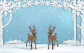 Paper art of cute reindeer with snow and snowflake background illustration