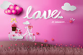 Paper art of happy valentine day balloon flying over bicycle and grass with heart float on the sky.