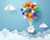 Paper art of house hanging with colorful balloon