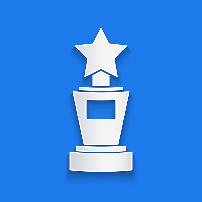 Paper cut Award cup icon isolated on blue background. Winner trophy symbol. Championship or competition trophy. Sports achievement sign. Paper art style. Vector Illustration