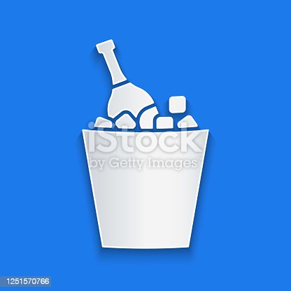 istock Paper cut Bottle of champagne in an ice bucket icon isolated on blue background. Paper art style. Vector Illustration 1251570766