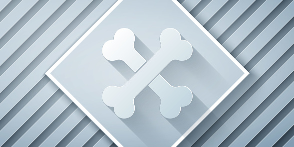 Paper cut Crossed human bones icon isolated on grey background. Paper art style. Vector