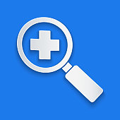 Paper cut Magnifying glass for search medical icon isolated on blue background. Hospital search. Paper art style. Vector Illustration