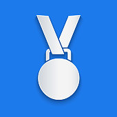 Paper cut Medal icon isolated on blue background. Winner symbol. Paper art style. Vector Illustration