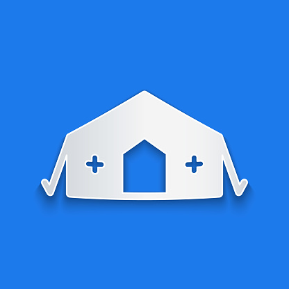 Paper cut Military medical tent providing first aid to a patient icon isolated on blue background. Medical tent free aid to people. Paper art style. Vector