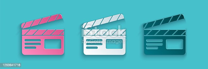istock Paper cut Movie clapper icon isolated on blue background. Film clapper board. Clapperboard sign. Cinema production or media industry. Paper art style. Vector Illustration 1253641718
