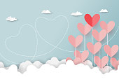 Paper art style of valentine's day greeting card and love concept.Origami floating hearts from clouds on blue sky background.Vector illustration.