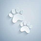 istock Paper cut Paw print icon isolated on grey background. Dog or cat paw print. Animal track. Paper art style. Vector 1289592020