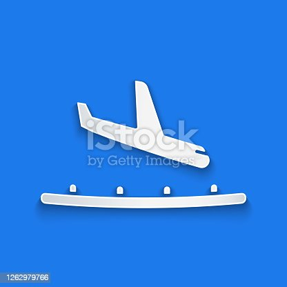 Paper cut Plane landing icon isolated on blue background. Airplane transport symbol. Paper art style. Vector Illustration