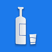 Paper cut Whiskey bottle and glass icon isolated on blue background. Paper art style. Vector Illustration