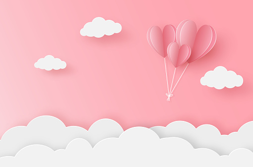 Paper heart balloon flying on the pink sky
