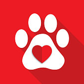 Vector illustration of a white paw print with a red folded paper heart on it on a square red background.