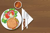 Paper Plate Of Food On A Wood Background. hamburger and salada