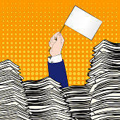 Paperwork. Businessman hand with white flag. Office desk loaded of paperwork , invoices and a lot of papers, documents. Pop art. Overworked man. Time managementHand of caucasian businessman emerging from office desk loaded of paperwork , invoices and a lot of papers and documents holding message card asking for help.