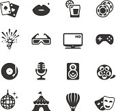 Sixteen illustrations representing entertainment are shown here.  All illustrations are a dark grey and shown on a white background.  The top row contains two aces, lips with a beauty mark, a movie projector and two movie reels.  Row two contains fireworks, 3D glasses, an HD monitor and a handheld gaming device.  Row three has a record player, a microphone, a speaker and a movie reel.  The bottom row contains a globe with a tower on top of it, a circus tent, a hot air balloon and the comedy and tragedy masks representing drama.