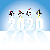 Four Happy Party Penguins wearing Santa Claus Hats Dancing on top of Frozen Year 2020 made in Snow casting long shadows on Blue Horizon
