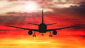 Passenger plane is flying, against the background of sunset. Airplane silhouette vector