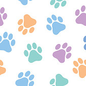 Vector seamless pattern of pastel colored paw prints.