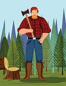 Paul Bunyan Style Lumberjack In the Woods With An Axe. He stands in front if a small forest. There is a chopped tree at the left and he holds his axe on his shoulder. Vertical