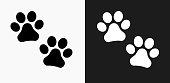 Paw Prints Icon on Black and White Vector Backgrounds. This vector illustration includes two variations of the icon one in black on a light background on the left and another version in white on a dark background positioned on the right. The vector icon is simple yet elegant and can be used in a variety of ways including website or mobile application icon. This royalty free image is 100% vector based and all design elements can be scaled to any size.