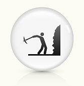 Person Mining Icon on simple white round button. This 100% royalty free vector button is circular in shape and the icon is the primary subject of the composition. There is a slight reflection visible at the bottom.