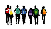 A bunch of students walk together with colorful backpacks on their back