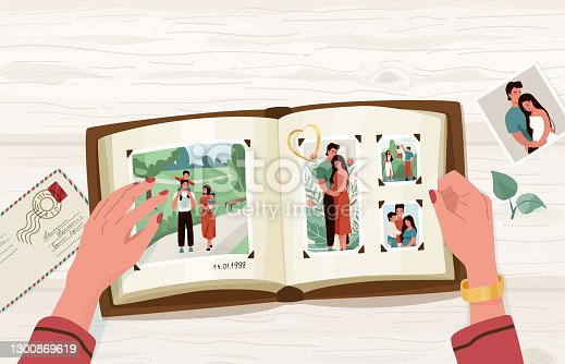istock Photo album with family photographs, vector illustration in simple cartoon flat style with empty blank space at the top. Female hands holding open memorable book. View from above 1300869619
