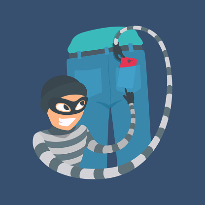 Pickpocket thief pulls a smartphone from a jeans back pocket. The criminal person in a mask, a cap, a striped turtleneck smiles.
