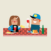 man and woman sitting on a rug having a picnic
