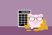 istock Piggy bank wears eyeglasses with a stack of coins and a calculator 1217184247