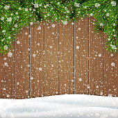 Christmas greeting card template with branches of a Christmas tree, snowdrift on a wooden background.