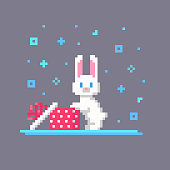 istock Pixel art Christmas rabbit opened the box. 1287318549