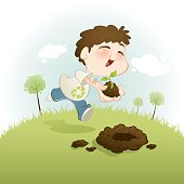 Child with recycle symbol t-shirt planting a tree on a grass field.  (exclusively on istockphoto only)