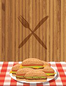 Platter Of Hamburgers On A Red plaid tablecloth. There is a grey fork and knife on a wood background.