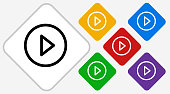 Play Color Diamond Vector Icon. The icon is black and is placed on a diamond vector button. The button is flat white color and the background is light. The composition is simple and elegant. The vector icon is the most prominent part if this illustration. There are five alternate button variations on the right side of the image. The alternate colors are red, yellow, green, purple and blue.