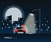 Police car standing under the lantern light, surrounded by a night city silhouette and shining moon. Stylish vector illustration with light effects and simple details.