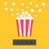 Popcorn popping. Film strip. Red yellow box. Cinema movie night icon in flat design style. Yellow background. Vector illustration