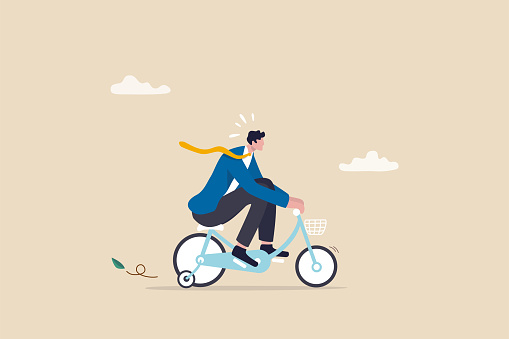 Practice, training or effort for career growth or business success, entrepreneur, amateur begin or start new business concept, newcomer businessman practice riding child bicycle with training wheels.