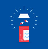 medicine, healthcare and pharmacy concept - pills and of drugs in shape of the heart white tablets are laid out in the shape of a heart and white plastic jar on a blue background with copy space