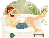 """A pretty young woman reads a magazine, lounged on the sofa with her hot coffee close by"""