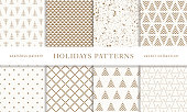 Set of winter holiday seamless patterns. Merry Christmas and Happy New Year. Collection of simple geometric textured backgrounds with golden color. Vector illustration. EPS 10