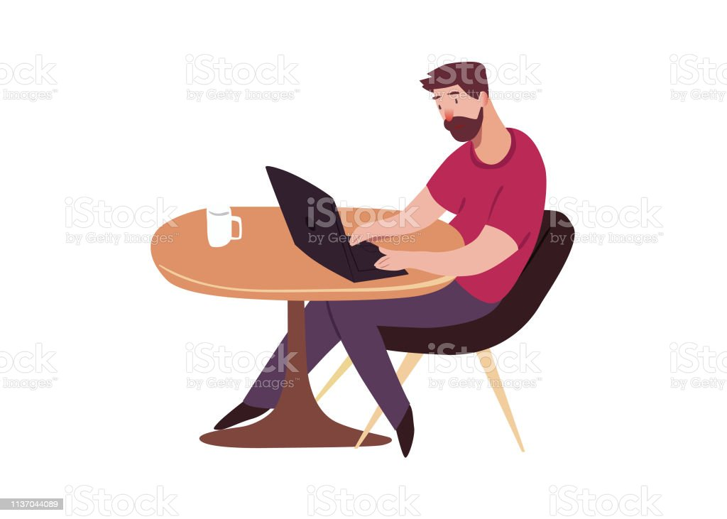 Programmer. Man sits in a chair at table with the laptop and a cup of...