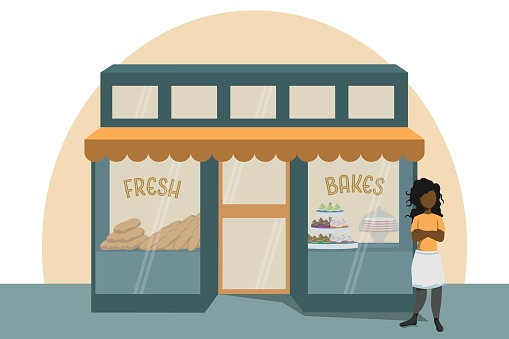 Proud bakery owner stands outside of bakery