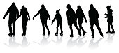 Large group of people ice skating in silhouettes