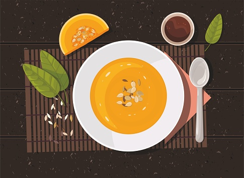 Pumpkin soup with spoon on table. Top view.