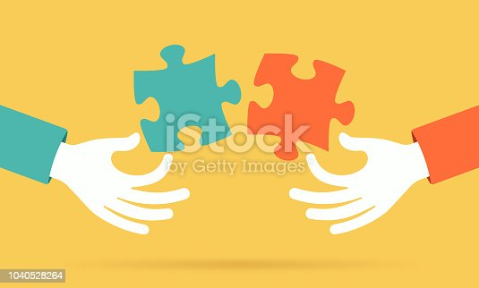 Hands putting a puzzle together teamwork concept.