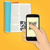 smartphone scanning qr code from a magazine on yellow background. the thumb is tapping on the screen, other fingers are behind the phone.