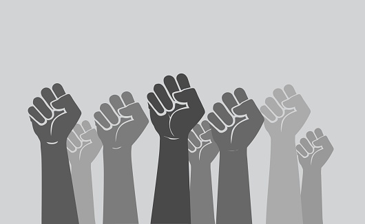 Racially-diverse human hands and fists raised in the air - people protesting. Concept of solidarity, civil unrest, diversity and inclusion.