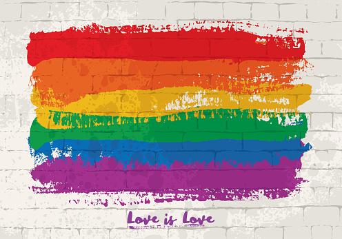 Rainbow flag brush strokes on a bricked wall